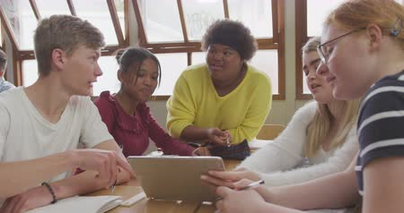 secondaire : Front view of a multi-ethnic group of teenage male and female school pupils in a classroom, sitting at a table working together, using a tablet computer, talking and smiling, in slow motion