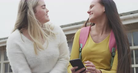 schoolyard : Front view close up of two Caucasian female school pupils, one with a schoolbag, hanging out, talking and looking at a smartphone together in their school playground at break time, in slow motion Stock Footage