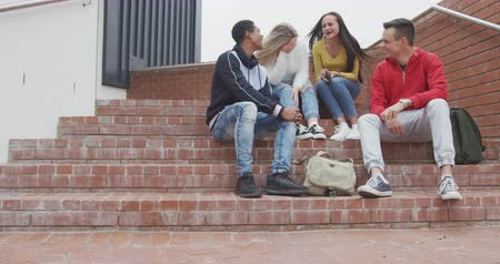 recess : Front view of a multi-ethnic group of teenage male and female school pupils with schoolbags hanging out and talking, sitting on steps in their school grounds, in slow motion