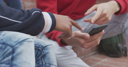 recess : Side view mid section of a mixed race and a Caucasian teenage male school pupil hanging out together, talking and using a smartphone, sitting on steps in their school grounds, in slow motion Stock Footage