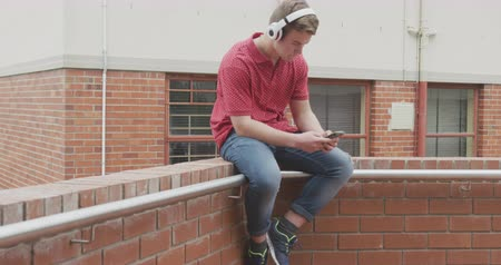 schoolyard : Side view of a Caucasian teenage male school pupil, using a smartphone and listening to music on headphones, sitting on a wall in the school grounds on a sunny day, in slow motion Stock Footage