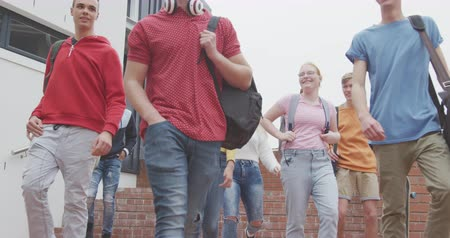 schoolyard : Front view of a multi-ethnic group of teenage male and female school pupils with schoolbags hanging out and talking, walking down steps in their school grounds, in slow motion