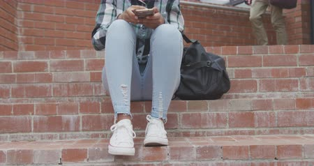 vzdělávat : Front view of a African American teenage female school pupil, using a smartphone and listening to music on headphones, sitting on steps with her bag in the school grounds on a sunny day, a male pupil walking in the background, in slow motion Dostupné videozáznamy