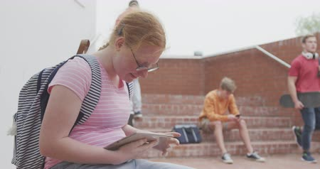 recess : Side view of a Caucasian teenage female school pupil, using tablet, with classmates in the background, sitting in their school grounds on a sunny day, in slow motion Stock Footage