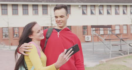 schoolyard : Front view of a Caucasian female and male school pupil with schoolbags hanging out, talking and using a smartphone together in their school grounds on a sunny day, the boy with his arm around the girl, and both smiling, in slow motion Stock Footage
