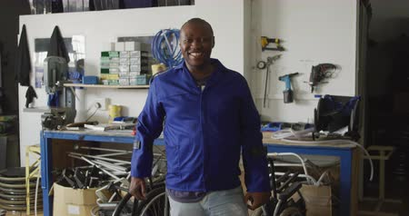 amputee : Portrait of an African American male worker in a workshop at a factory making wheelchairs, looking to camera and smiling, standing on crutches