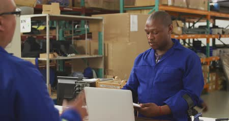 kule : Front view of an African American male worker and a mixed race male worker in a storage warehouse at a factory making wheelchairs, standing and talking across a counter, one man passing the other a clipboard and giving some instructions. The man behind th Wideo