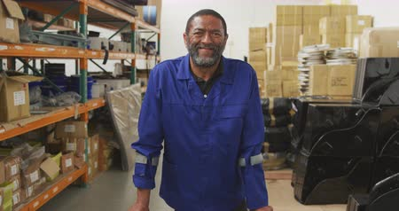 kule : Portrait of an African American male worker in a storage warehouse at a factory making wheelchairs, looking to camera, smiling and laughing, standing on crutches