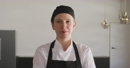 beyazlar : Portrait close up of a Caucasian female chef wearing chefs whites, a black hat and apron, standing in a cookery class, looking to camera and smiling, in slow motion Stok Video