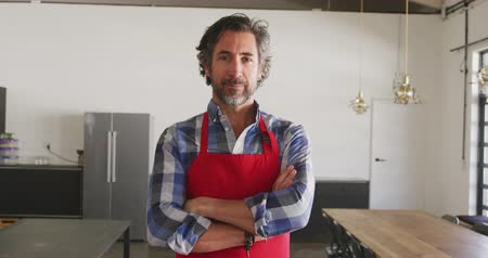 armen over elkaar : Portrait of a senior Caucasian man with a beard, wearing a red apron and a checked shirt, standing in cookery class with arms crossed, looking to camera and smiling, in slow motion