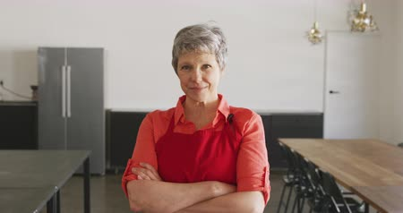 armen over elkaar : Portrait of a senior Caucasian woman wearing a red apron, standing in cookery class with arms crossed, looking to camera and smiling in slow motion Stockvideo