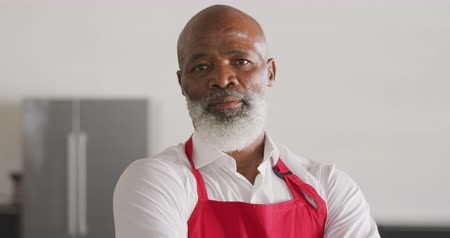 armen over elkaar : Portrait close up of a senior African American man with a white beard, wearing a red apron, standing in cookery class with arms crossed, looking to camera and smiling, in slow motion