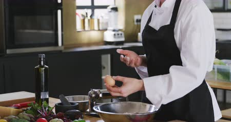 beyazlar : Side view close up of a Caucasian female chef wearing chefs whites, black hat and apron standing in cookery class holding an egg and explaining what to do in slow motion