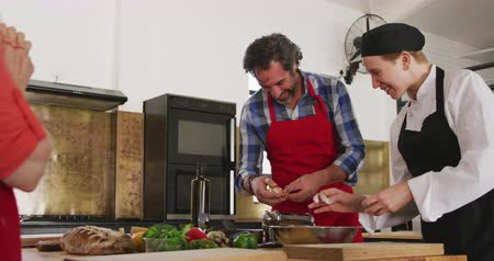 comida : Side view of a senior Caucasian man and Caucasian female chef in a kitchen during a cookery class, the female chef watching her male student breaking an egg and both laughing, in slow motion Stock Footage