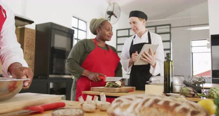 american cuisine : Side view of a senior African American woman at a cookery class preparing food in a kitchen, talking with a Caucasian female chef showing her a tablet computer, a senior African American man mixing food in a bowl in the foreground, in slow motion