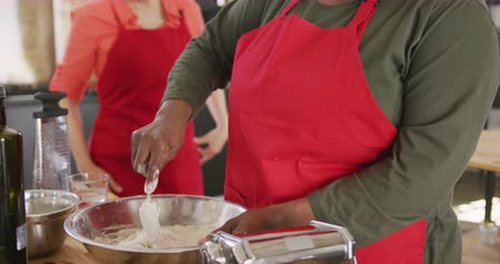working together : Front view close up of a senior African American and a senior Caucasian woman interacting during a cookery class, one of them cooking, the other watching and leaning on her shoulder, both smiling, in slow motion