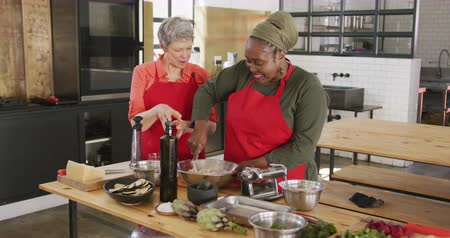 top chef : Front view of a senior African American and a senior Caucasian woman interacting during a cookery class, one of them cooking, the other watching and talking to her, both smiling, in slow motion