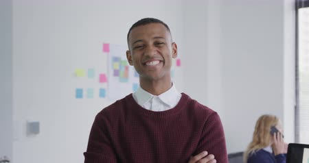 armen over elkaar : Portrait of a happy mixed race man working in a creative office, looking at camera smiling, his female colleague working at her desk in the background