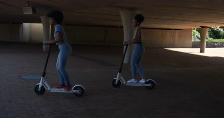 companionship : Side view of two mixed race women enjoying free time in a urban park on a sunny day together, riding electric scooters, slow motion