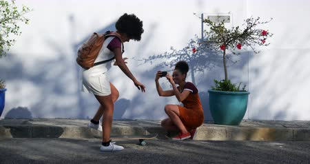 стенд : Side view of two mixed race women enjoying free time on a street on a sunny day together, skateboarding, taking photos, slow motion