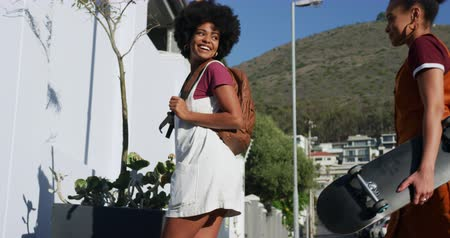 provést : Side view of two mixed raced women enjoying free time on a street on a sunny day, walking, talking and carrying a skateboard, slow motion