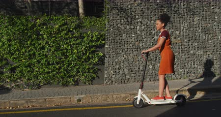 içerik : Side view of mixed race woman enjoying free time on a street on a sunny day, riding on electric scooter, slow motion Stok Video