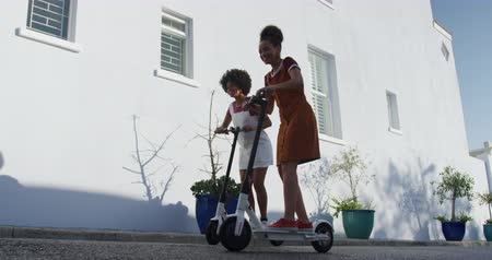 companionship : Low angle side view of two mixed race women enjoying free time on a street, on a sunny day together, riding electric scooters, slow motion