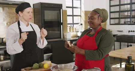 culinária : Side view of a senior African American woman and a Caucasian female chef talking during cookery class, the African American woman preparing dough and laughing, while the chef watches, dances and talks, in slow motion