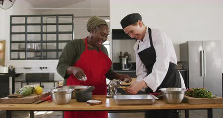 culinária : Front view of a senior African American woman and a Caucasian female chef during a cookery class, rolling dough through a pasta machine together and laughing, in slow motion