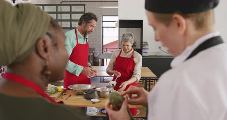 top chef : Front view of a senior adult Caucasian man and woman during preapring food together during a cookery class, while a senior African AMerican woman talks with a Caucasian female chef in the foreground, focus on the background, in slow motion