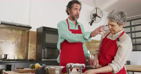 culinária : Front view of a senior Caucasian woman and man working together during a cookery class, adding flour to dough, and rolling with a pasta machine, joking and laughing in slow motion