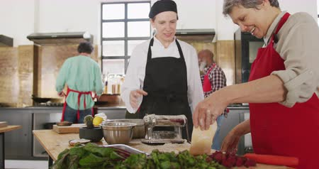 culinária : Side view of a senior Caucasian woman and a Caucasian female chef during a cookery class in a restaurant kitchen, the senior woman rolling dough through a pasta machine, while the chef shows her approval, with other adult students working in the backgroun