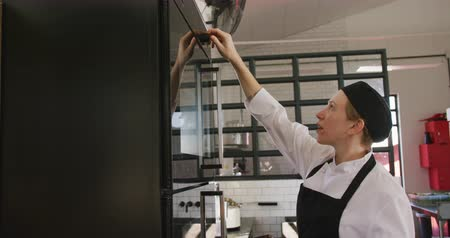 discar : Side view of a Caucasian female chef at a cookery class in a restaurant kitchen, turning an oven on, pressing buttons and turning a dial to set the temperature, in slow motion