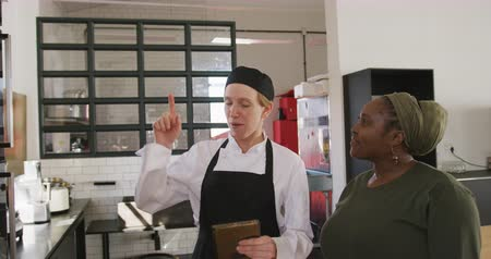 working together : Side view of a senior African American woman and a Caucasian female chef at a cookery class in a restaurant kitchen, standing next to an oven and looking at a recipe on a tablet computer, in slow motion