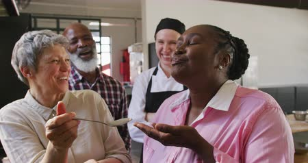 culinária : Front view of a senior African American woman enjoying a spoonful of a hot dish given to her by a senior Caucasian woman during a cookery class in a restaurant kitchen, with a senior African American man and a Caucasian female chef wearing chefs whites an Stock Footage