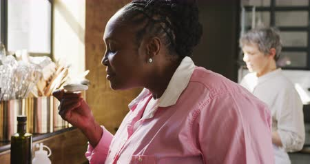 kuchařství : Side view close up of a senior African American woman during cookery class in a restaurant kitchen, smelling a spoonful of a hot dish with her eyes closed and laughing, a Caucasian female chef in the background, in slow motion Dostupné videozáznamy