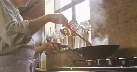 wok food : Side view close up of a senior Caucasian woman during cookery class in a restaurant kitchen, standing at a hob stir frying vegetables in a wok using a wooden spatula, backlit by sunlight from a window, in slow motion