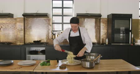plating food : Front view of a Caucasian female chef during cookery class in a restaurant kitchen, arranging freshly cooked pasta on a plate with tongs, in slow motion