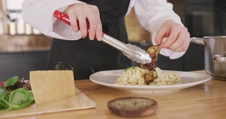 plating food : Front view mid section of a Caucasian female chef during a cookery class in a restaurant kitchen, using tongs and adding fried vegetables to freshly cooked pasta, in slow motion