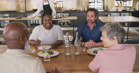 socialising : High angle view of a multi-ethnic group of senior adults at a cookery class, sitting at a table, talking to each other and relaxing after the class, while a Caucasian female chef is preparing food in the background, in slow motion
