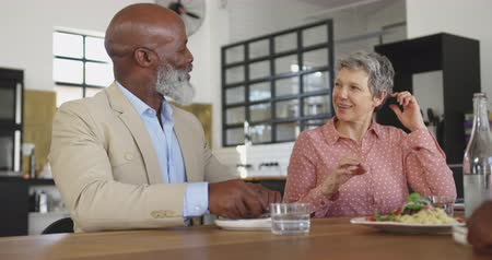 culinária : Front view of a senior Caucasian woman and a senior African American man, sitting at a table relaxing after a cookery class in a restaurant kitchen, talking and trying their food, in slow motion Stock Footage