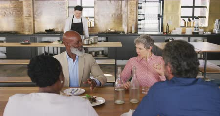 culinária : High angle view of a multi-ethnic group of senior adults at a cookery class, sitting at a table, talking to each other and relaxing after the class, while a Caucasian female chef is preparing food in the background, in slow motion