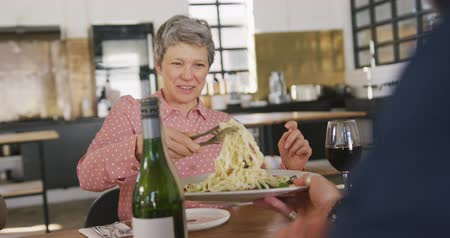socialising : Front view of a senior adult Caucasian woman sitting at a table relaxing with her colleagues after a cookery class in a restaurant kitchen, talking and serving freshly cooked pasta they have prepared, in slow motion Stock Footage
