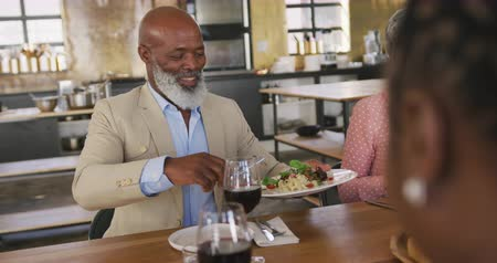 lunchen : Front view of a senior African American man and a senior Caucasian woman sitting at a table relaxing with their colleagues after a cookery class in a restaurant kitchen, talking and serving freshly cooked pasta they have prepared, in slow motion Stockvideo