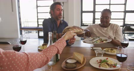 lunchen : Front view of a senior Caucasian man and a senior African American woman sitting at a table relaxing with their colleagues after a cookery class in a restaurant kitchen, talking and serving food they have prepared, in slow motion Stockvideo