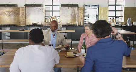 kırmızı şarap : Front view of a multi-ethnic group of senior adults sitting at a table relaxing with their colleagues after a cookery class in a restaurant kitchen, talking and serving each other the food they have prepared, in slow motion Stok Video