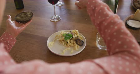 fűszerezés : Over the shoulder view of a senior adult Caucasian woman sitting at a table relaxing with her colleagues after a cookery class in a restaurant kitchen, seasoning a dish of freshly cooked pasta they have prepared together, in slow motion