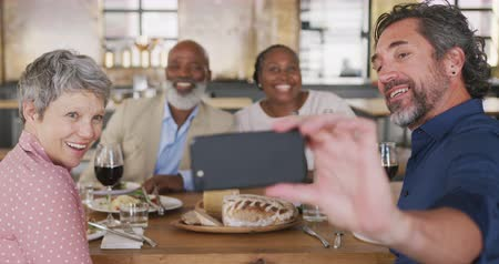 socialising : Front view of a multi-ethnic group of happy senior adults sitting at a table relaxing with their colleagues after a cookery class in a restaurant kitchen and taking a selfie, in slow motion Stock Footage