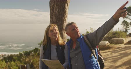 négy : Front view of a senior Caucasian couple enjoying time in nature together, standing in forest during a hike, checking the map and pointing in slow motion