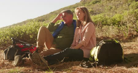 quatro : Side view of a senior Caucasian couple enjoying time in nature together, sitting on a meadow during a hike with backpacks and Nordic walking sticks, smiling in slow motion
